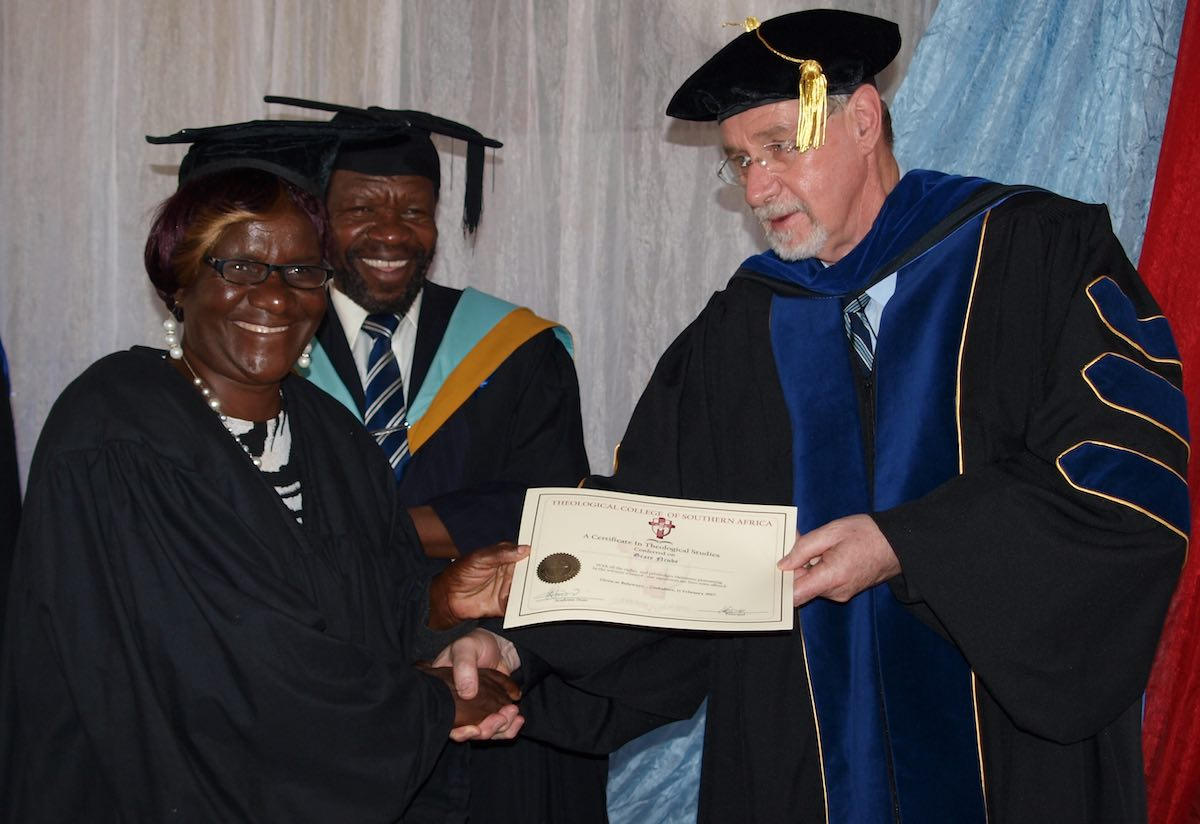 A newly graduated student receives her certificate